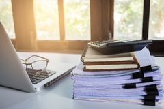 堆在现代白色办公桌上的业务报告文件夹 免版税库存图片