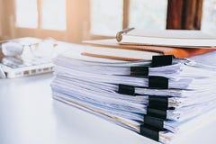 堆在现代白色办公桌上的业务报告文件夹 免版税库存照片