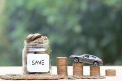堆在玻璃瓶和微型汽车模型的硬币新的汽车的金钱在绿色背景,攒钱,财务和汽车贷款, 免版税图库摄影