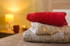 堆在用光装饰的床上的温暖的被编织的毛线衣和灯、杯子和蜡烛在背景中 图库摄影