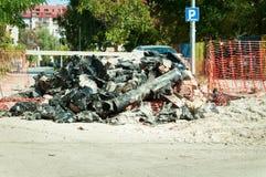 堆在用新的管道挖掘从地面和替换的街道上的老管子 免版税库存图片