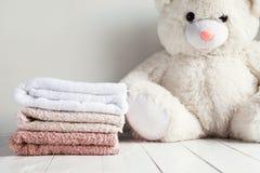 堆在白色木桌上的温泉毛巾与白色软的玩具涉及背景 儿童的洗涤物概念 免版税库存照片