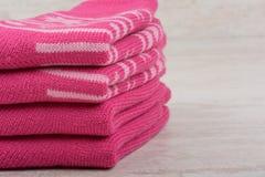 堆在白色木背景的桃红色羊毛袜子 免版税库存图片