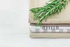 堆在白色木表室内设计的亚麻布和棉花洗碗布餐巾新鲜的罗斯玛丽枝杈 免版税库存图片