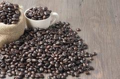 堆在白色杯子和棕色大袋的咖啡豆 免版税库存照片