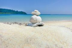 堆在白色沙子的小卵石在海滩 库存图片
