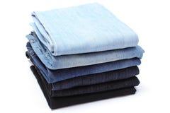 堆在白色背景的蓝色牛仔裤 库存照片