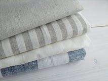 堆在白色背景的镶边白色灰色蓝色亚麻制棉织物 库存照片