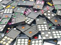 堆在白色背景的黑塑料多米诺 免版税库存图片