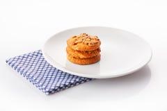 堆在白色陶瓷板材的三个自创花生酱曲奇饼在蓝色餐巾 免版税图库摄影
