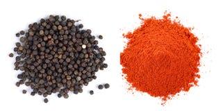 堆在白色backg的红色辣椒粉粉末和黑胡椒种子 免版税库存照片