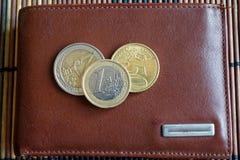 堆在皮革棕色钱包的欧洲硬币 免版税库存照片