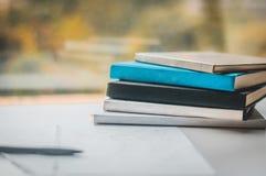 堆在窗口前面的书在笔和纸旁边 免版税库存照片