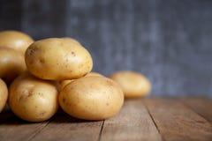 堆在老木桌上的土豆 免版税库存照片