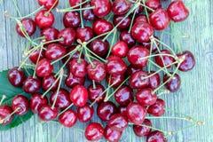 堆在老木桌上的红色成熟快活的樱桃 图库摄影
