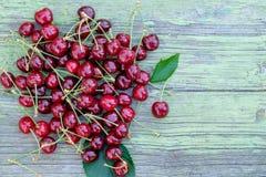 堆在老绿色木桌上的红色成熟快活的樱桃 顶视图 免版税库存图片