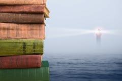 堆在自然backgroundWisdom概念的书-堆在海和灯塔背景的书 免版税库存图片