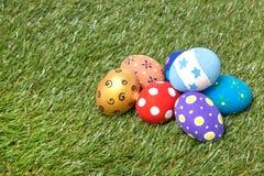 堆在草的五颜六色的手工制造复活节彩蛋 免版税库存照片