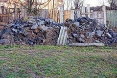 堆在草的建筑废料在篱芭附近的围场 库存照片