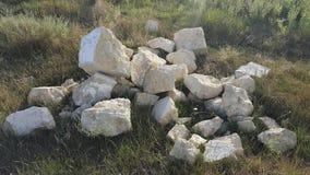堆在草的石头 生活位置 废墟 免版税库存照片