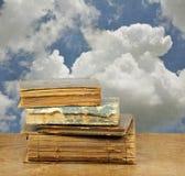 堆在蓝色多云天空的旧书 文本的空间 免版税库存照片