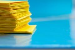 堆在蓝色桌上的黄色纸 免版税库存图片