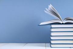 堆在蓝色背景的书 在堆顶部的一本暗藏的书 免版税图库摄影