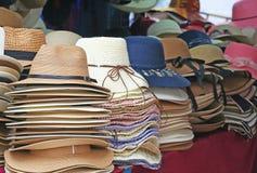 堆在街市上的品种帽子 免版税库存图片