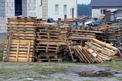 堆在街道上的灰色老木板台在房子附近的围场 免版税库存照片