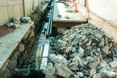 堆在街道分区供暖管道系统重建站点的沥青石头 免版税库存图片