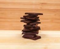 堆在表上的黑暗的巧克力片 库存照片