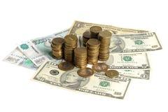 堆在钞票的硬币 库存照片