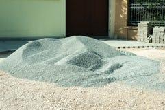 堆在铺重建站点的街道上的石渣石头在城市 免版税库存图片