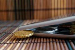 堆在镜子的欧洲硬币反射在广角背景衡量单位是10欧分的木竹桌上的钱包谎言 免版税库存照片