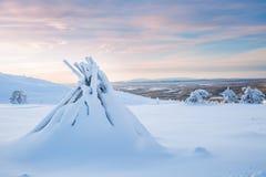 堆在雪的木柴盖子与剧烈的天空在一个冬日在拉普兰芬兰北欧 图库摄影