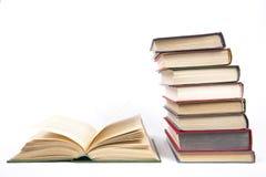 堆在颜色盖子的书在开放书旁边 库存图片