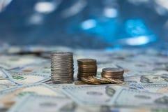堆在驱散的硬币在明亮的蓝色背景的一百元钞票与bokeh作用 库存图片