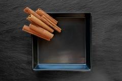 堆在黑石表面背景安置的黑色的盘子安置的干肉桂条 库存照片