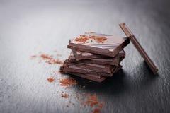 堆在黑暗的石背景的巧克力大块用可可粉,特写镜头 库存图片