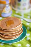 堆在绿色板材的薄煎饼有蜂蜜小河的 库存照片