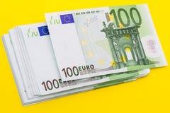堆在黄色的100张欧洲钞票 库存图片