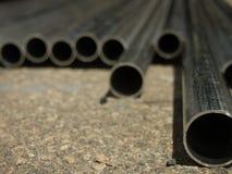 堆在建造场所的许多管子 免版税库存图片