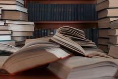 堆在bookshelve桌背景的许多旧书  库存照片