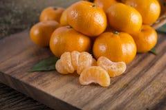 堆在c的整个和被剥皮的新鲜的蜜桔或橘子 库存照片