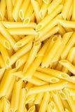 堆堆未煮过的意大利人Penne面团 明亮的充满活力的黄色颜色 顶视图 食物背景样式 免版税库存图片