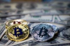 堆堆积在一百美元钞票的金黄bitcoin 唯一硬币在锋利的焦点的面对照相机 免版税库存照片