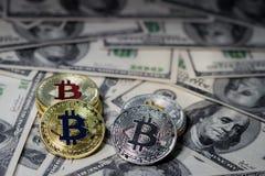 堆堆积在一百美元钞票的金黄bitcoin 唯一硬币在锋利的焦点的面对照相机 图库摄影