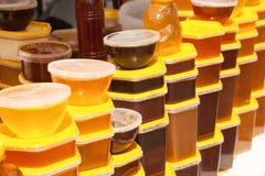 堆塑胶容器用蜂蜜在农夫食物市场上 库存图片