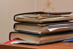 堆学生的老笔记本在桌上的 图库摄影