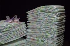 堆尿布和安慰者 库存图片